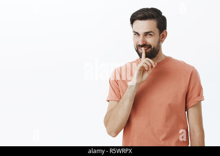 Keep it our secret. Portait of mysterious and cheeky bearded guy squinting tricky and smiling as showing shh gesture with index finger on mouth, makin - Stock Photo
