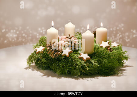 Third Advent - decorated Advent wreath from fir and evergreen branches with white burning candles, tradition in the time before Christmas, warm backgr - Stock Photo