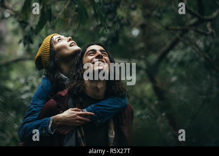 Happy young guy carrying his woman on back in the forest and enjoying the rain. Lovely couple piggybacking in the park under rain. - Stock Photo