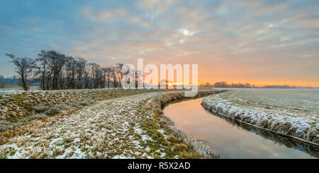 Meandering River in Frozen  landscape on early morning with rising sun under beautiful sky - Stock Photo