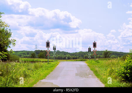 Empty rural level crossing without barriers,  rail crossing, view with blue sky and clouds, countryside. Cross of Saint Andrew and traffic lights. - Stock Photo
