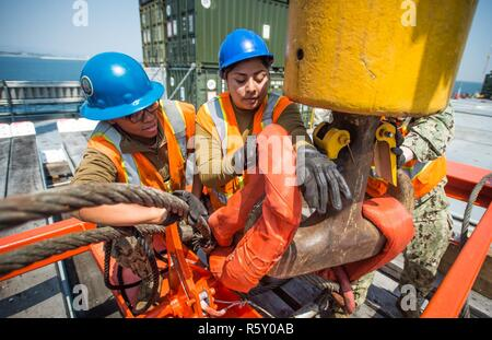 U.S. Navy Sailors, assigned to Navy Cargo Handling Battalion 1, attach a crane link to the USNS Pililaau's (T-AKR 304) crane off the coast of Dogu Beach, Republic of Korea, during Operation Pacific Reach Exercise 2017 (OPRex17) April 13, 2017. OPRex17 is a bilateral training event designed to ensure readiness and sustain the ROK-U.S. alliance by exercising an area distribution center, an air terminal supply point, combined joint logistics over-the-shore, the use of rail, inland waterways, and the coastal lift operations to validate the operational reach concept. - Stock Photo