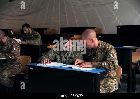Sgt. Christopher Beseda, a U.S. Army Paratrooper from Alpha Company, 1st Battalion, 503rd Infantry Regiment, 173rd Airborne Brigade reviews course material with an Italian Army Folgore Brigade Paratrooper during  the Jumpmaster Course at Gamerra Folgore Brigade Airborne School, Pisa, Italy, April 13, 2017. ( - Stock Photo