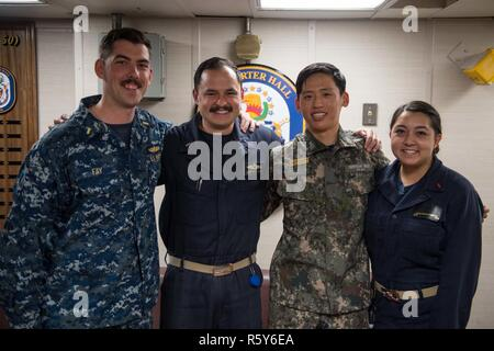 5TH FLEET AREA OF OPERATIONS (April 20, 2017) From left, Ensign Brendan Fay, Lt. j.g. Ivan Subildea, Lt. j.g. Sung Bok Lee and Ensign Cassandra Fisbeck pose for a portrait. The four officers graduated from the United States Naval Academy in the 24th company, and reunited by chance at sea aboard the amphibious dock landing ship USS Carter Hall (LSD 50) during Counter-piracy Validation Exercise 2017. - Stock Photo