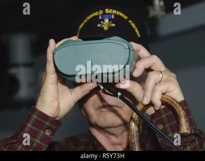 Retired U.S. Army 1st Sgt. Claude Quick, Legion of Valor member, looks through simulation binoculars at the Maritime Intermodal Training Department while on a tour at Joint Base Langley-Eustis, Va., April 21, 2017. Each year, members of the Legion of Valor gather for an annual convention to enhance their understanding of current military affairs and provide mentorship from personal accomplishments or failures. - Stock Photo