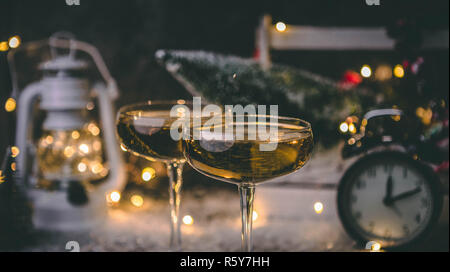 Picture of two champagne glasses on blurred background with Christmas tree, lantern, clock - Stock Photo