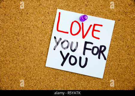 A yellow sticky note writing, caption, inscription Phrase LOVE YOU FOR YOU in black ext on a WHITE sticky note pinned to a cork notice board - Stock Photo