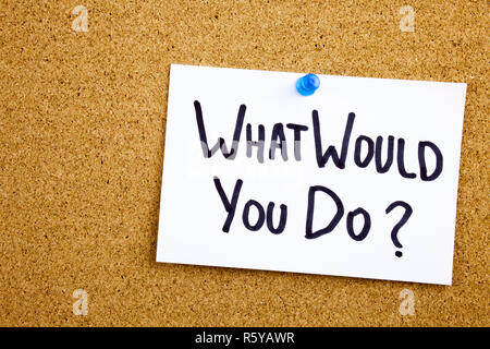 A yellow sticky note writing, caption, inscription Phrase WHAT WHOULD YOU DO in black ext on a sticky note pinned to a cork notice board - Stock Photo