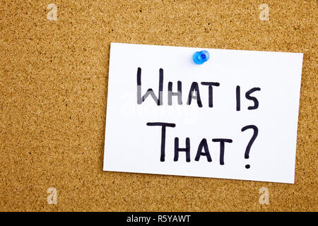 A yellow sticky note writing, caption, inscription Phrase WHAT IS THAT in black ext on a sticky note pinned to a cork notice board - Stock Photo