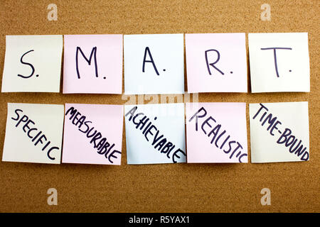 A yellow sticky note writing, caption, inscription Phrase SMART in black ext on a sticky note pinned to a cork notice board specific, measurable, attainable, recorded, timely colorful sticky notes on cork bulletin board - Stock Photo