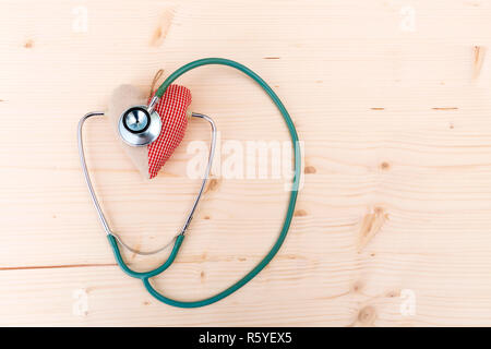 Stethoscope and red fabric heart lying on wooden table. Healthcare, cardiology and medical concept - Stock Photo