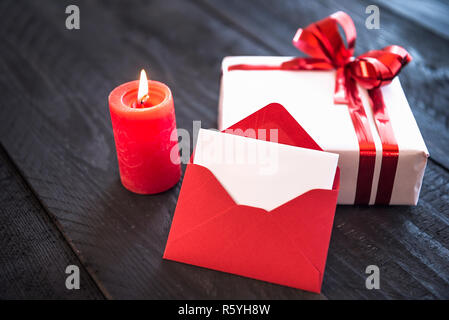Lit candle and blank letter - Stock Photo