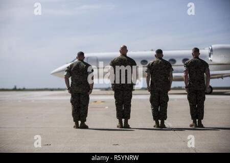 (From left to right) Sergeants Major John J. Elliot and Matthew A. Putnam, and Colonels Sean M. Salene and Daniel Q. Greenwood, stand at attention as Maj. Gen. Niel Nelson's plane taxis on Morón Air Base, Spain, April 16, 2017. Maj. Gen. Nelson, Commander of Marine Corps Forces Europe and Africa, arrived to attend the Special Purpose Marine Air-Ground Task Force-Crisis Response-Africa, transfer of authority ceremony the following day. - Stock Photo