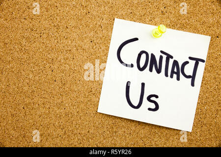 A yellow sticky note writing, caption, inscription Phrase CONTACT US in black ext on a sticky note pinned to a cork notice board - Stock Photo