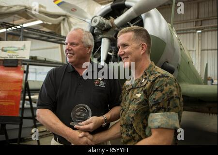 Robert Cramsie, left, a restoration volunteer with the Flying Leatherneck Aviation Museum and a board member of the Flying Leatherneck Historical Foundation, displays his award while shaking hands with Col. Jason Woodworth, commanding officer of Marine Corps Air Station Miramar, Calif., at the Flying Leatherneck Aviation Museum Restoration Facility at MCAS Miramar, Calif., April 21.   Cramsie received the Northrop Grumman Excellence in Volunteerism Award for volunteering more than 2,500 hours to restore a last-of-its-kind Douglas SBD-1 Dauntless dive bomber, reconstructed using blueprints, sal