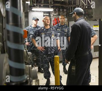 NORFOLK, Va. (April 26, 2017) -- Aviation Boatswain's Mate (Equipment) 1st Class Kenneth Williams, assigned to Pre-Commissioning Unit Gerald R. Ford (CVN 78), discusses with U.S. Fleet Forces Command Fleet Master Chief Paul Kingsbury the aircraft arresting gear (AAG) aboard Ford. - Stock Photo
