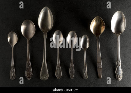 Different spoons on a black stone top view - Stock Photo
