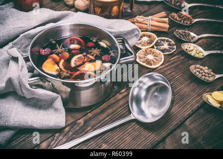 mulled wine in a pot with handles and an iron kitchen scoop - Stock Photo