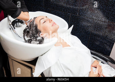 White woman getting a hair wash procedure in a beauty salon - Stock Photo