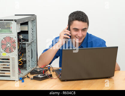 Young man technician working on broken computer and call the customer - Stock Photo