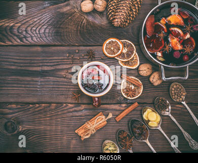 mulled wine and ingredients in iron spoons - Stock Photo