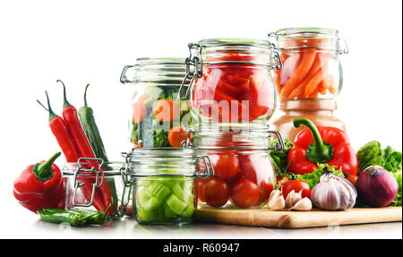 Jars with marinated food and raw vegetables isolated on white - Stock Photo