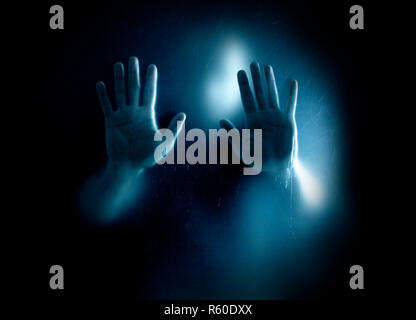 Shadowy figure trapped behind a dusty scratched glass - Stock Photo