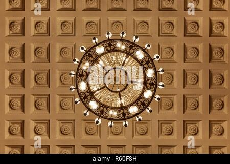 Chandelier on decoarted ceiling - Stock Photo