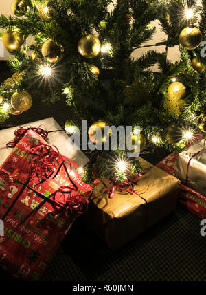 close up view of colorful presents under a beautifully decorated Christmas tree with baubles and lights - Stock Photo