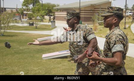 Lance Cpl. Rahkeim Crawford and Cpl. Devonte Harrison, tank crewmen, 1st Tank Battalion, play corn hole during the 1st Marine Division Association Barbecue at Victory Field aboard Marine Corps Air Ground Combat Center, Twentynine Palms, Calif., April 28, 2017. 1st Marine Division Association and unit Family Readiness Officers hosted the barbecue to build camaraderie and foster relationships between junior Marines, sailors and family members. - Stock Photo