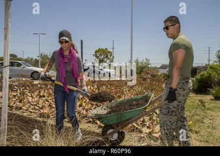 U.S. Marines, Sgt. Sarahi C. Escudero, left, with School of Infantry - West, and Cpl. Cesar Juarez, corporal of the guard, Lima Company, Headquarters and Support Battalion, SOI-WEST, lay mulch during the 'Weekend of Service' on Camp Pendleton, Calif., April 29, 2017. Community members from surrounding areas volunteered to perform maintenance and gardening projects at several locations across the base. - Stock Photo