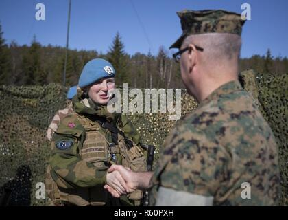 U.S Marine Col. Doug Bruun meets with a cadet of the Royal Norwegian Air Force Academy during a mock United Nations exercise in Giskaas, Norway, April 25, 2017. The cadets briefed Bruun on each of their post's status and organization. Marine Rotational Force Europe 17.1 (MRF-E) galvanizes the Marine Corps' long and close relationship with the Norwegian Armed Forces. - Stock Photo