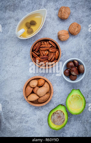 Selection food sources of omega 3 and unsaturated fats. super food high omega 3 and unsaturated fats for healthy food. Almond ,pecan ,hazelnuts,walnuts ,olive oil and avocado on stone background . - Stock Photo