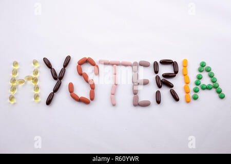 Conceptual Hand writing text caption inspiration Medical care Health concept written with pills drugs capsule word HYSTERIA season On white isolated background with copy space - Stock Photo
