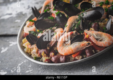 Paella in the metal plate on the metal background horizontal - Stock Photo