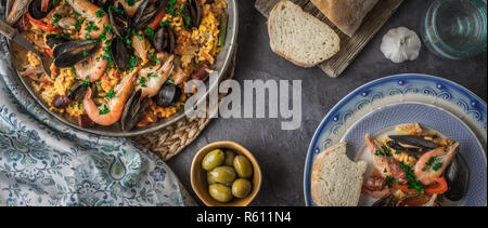 Plates with paella on the dark stone table with different accessories wide screen - Stock Photo