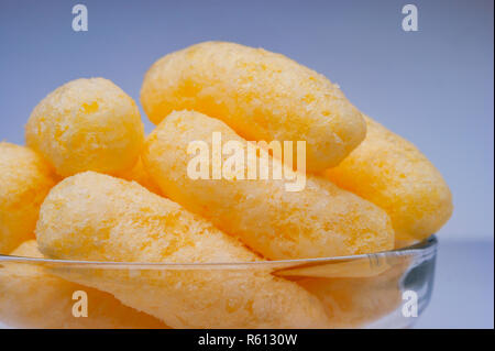 Zoomed Corn Puffs in a Glass Bowl. Crunchy Flavored Puffed Snacks. Party, Movie Snacks. - Stock Photo