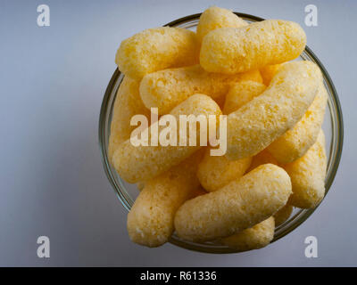 Corn Puffs in a Glass Bowl. Crunchy Flavored Puffed Snacks. Party, Movie Snacks. - Stock Photo