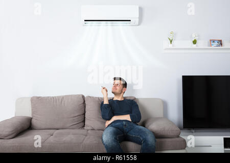 Man Sitting On Couch Operating Air Conditioner - Stock Photo