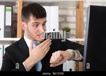 Worried Young Businessman Checking Time In His Watch - Stock Photo