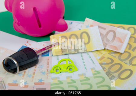 pink piggy bank with money, car key on a green carpet - Stock Photo