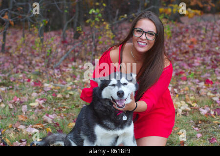 young woman red dress playing with a dog in a park - Stock Photo