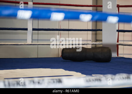 Empty Boxing Ring with Black Punching Bag on the Ground. - Stock Photo