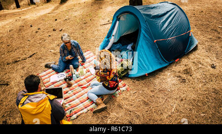 People enjoy free camping in the pines forest using technology laptop and mobile phoner and relaxed from the stress society - outdoor lifestyle for al - Stock Photo