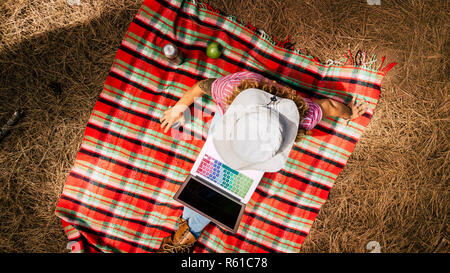 Top view of woman working on a laptop in the forest during travel or vacation - alternative office and freelance freedom work for modern digital nomad - Stock Photo