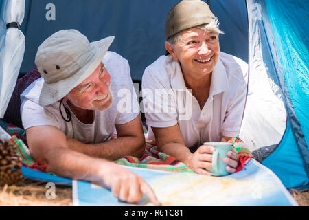couple of adult caucasian traveler inside a tent in free camping - happiness for cheerful people who love to discover the world - wanderlust lifestyle - Stock Photo