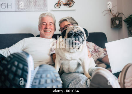 Caucasian senior couple sit on the couch with funny pug dog looking. Happiness with love for animals and best friend concept - home daily life with ni - Stock Photo