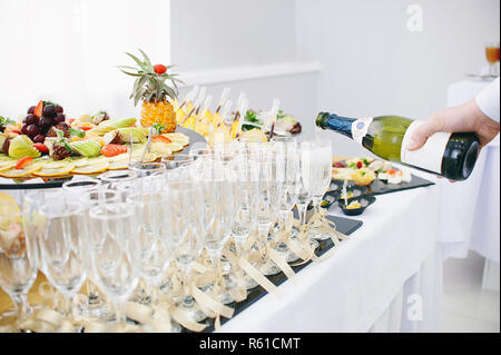 A beautiful fruit bar serving a festive table. The waiter pours champagne in wine glasses - Stock Photo