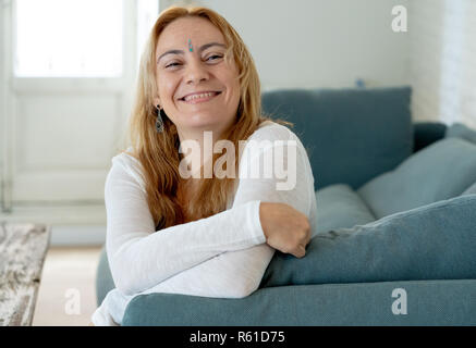 Portrait of beautiful caucasian woman with a bindi in the center of her forehead feeling happy and peaceful with her new healthy and spiritual lifesty - Stock Photo