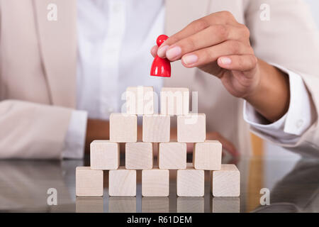 Businesswoman Placing Red Figure On Arranged Blocks - Stock Photo